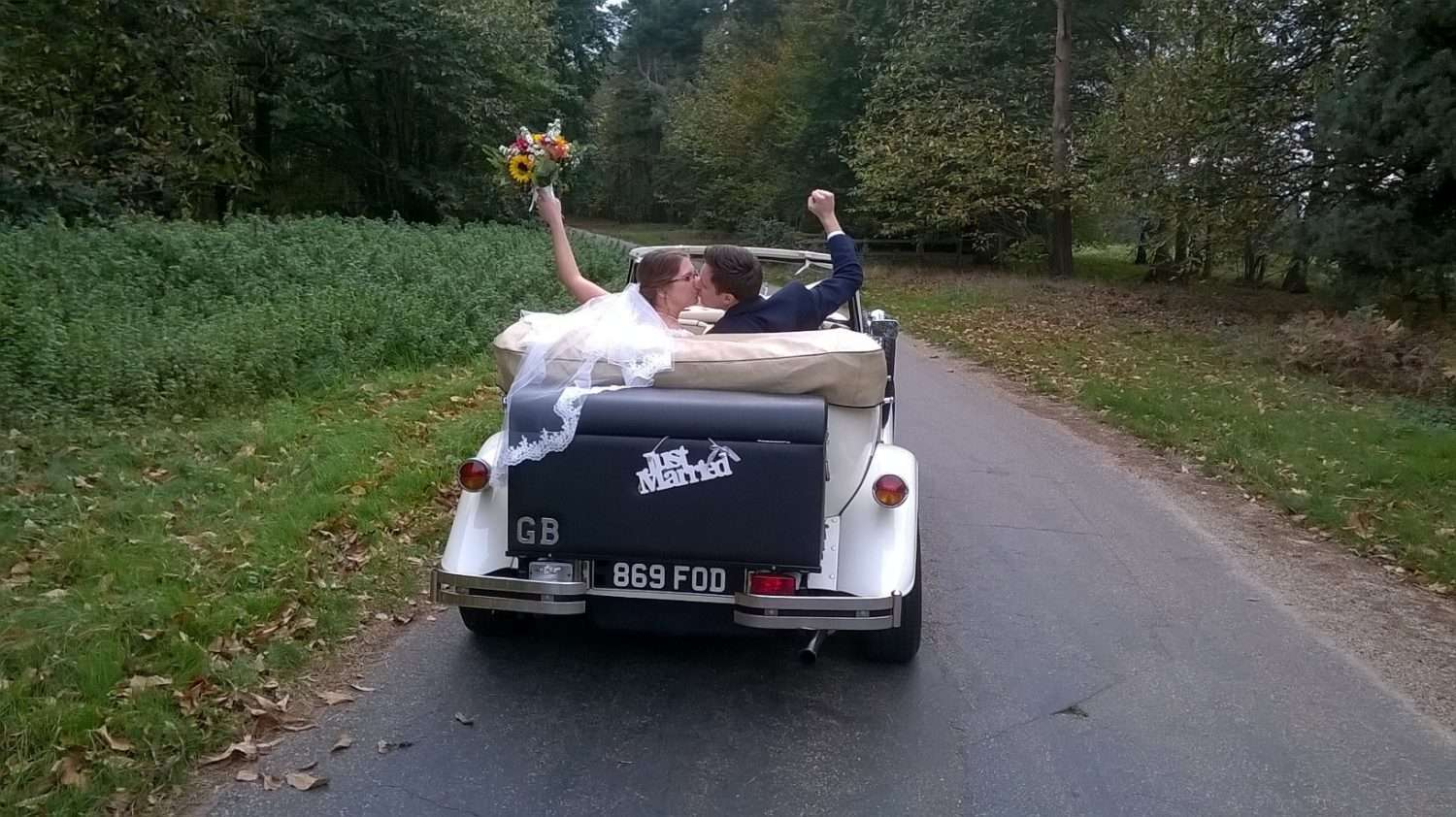 Bride & Groom driving down a road in a Beauford car with just married on the back.