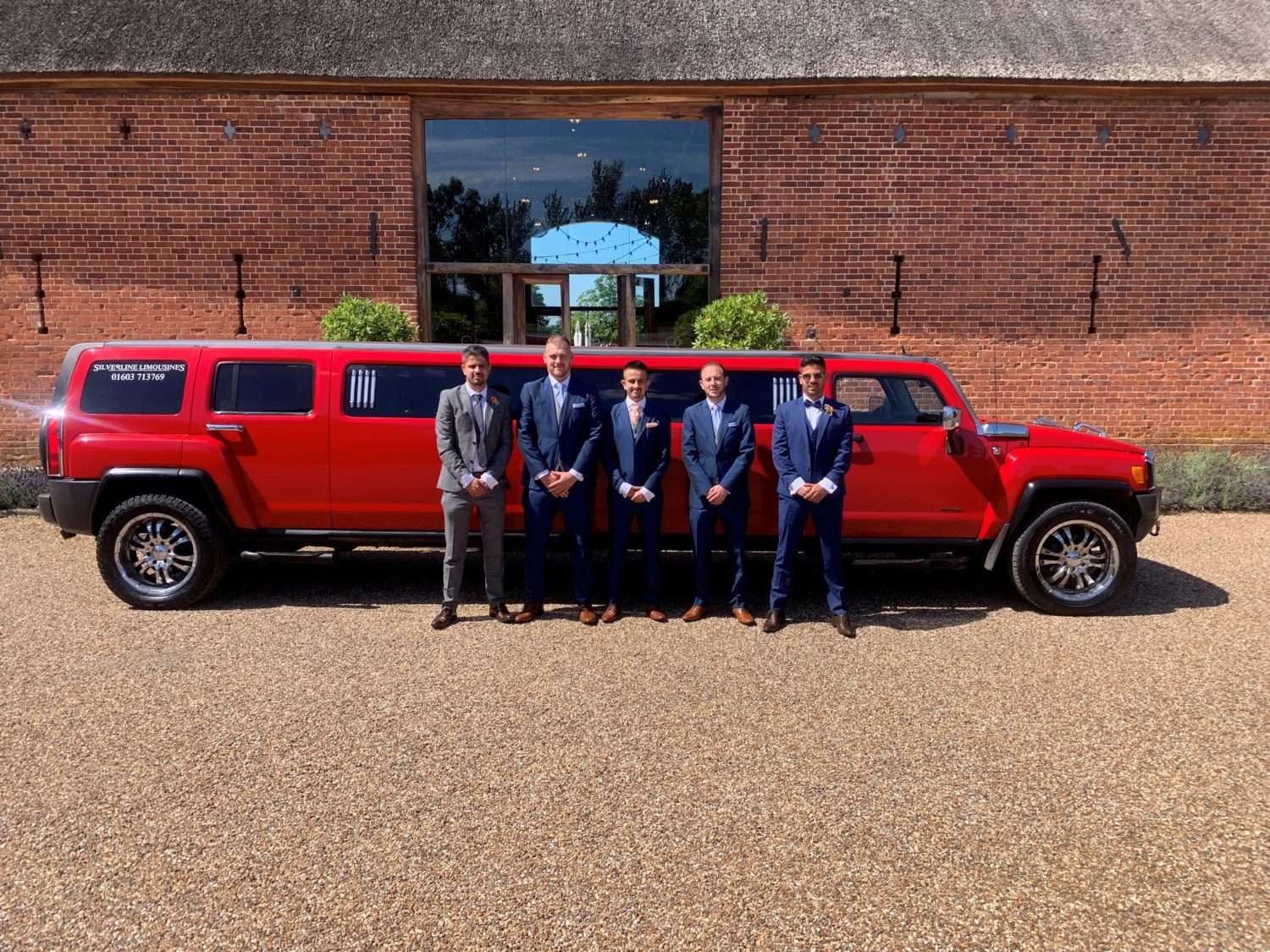 Grooms party lined up in front of Hummer at Southwood Hall in Norfolk